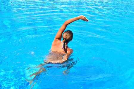 Exercise in the pool. Girl doing gymnastic exercises in the water. Active water sports. The Aqua-fitness for women. Archivio Fotografico