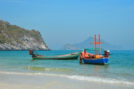 Scenic landscape with boats on the beach. Colorful wooden ships on the water. Tropical beach and fishing boats.
