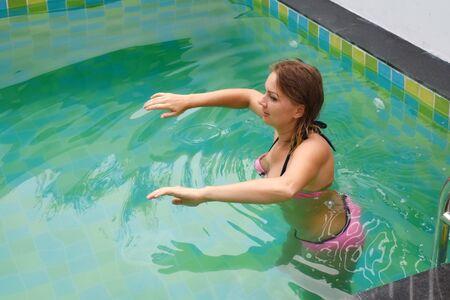 La donna va a fare sport in piscina. Ragazza che fa esercizi in acqua. Acquagym in piscina.