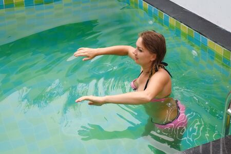 Woman goes in for sports in the pool. Girl doing exercises in the water. Aqua gym in the pool.