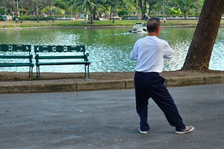 Thailand. Bangkok. January 2020. Asian male doing qigong exercises in the Park. The Chinese practice qigong in a public place.