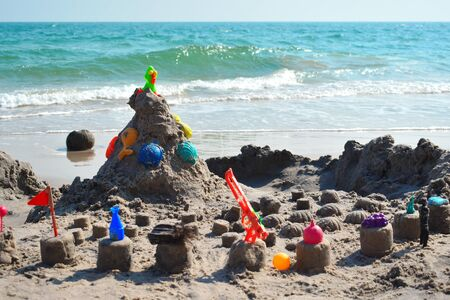 Sand castle on the beach. The children built a city on the sea. Children's toys on the beach. Marine families with children.