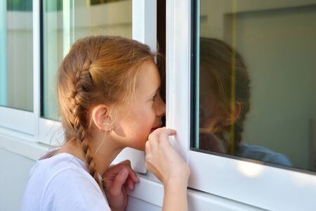 Cute child girl peeking. Beautiful girl peeping. The Sly glance of the child. The child spies. Hide-and-seek.