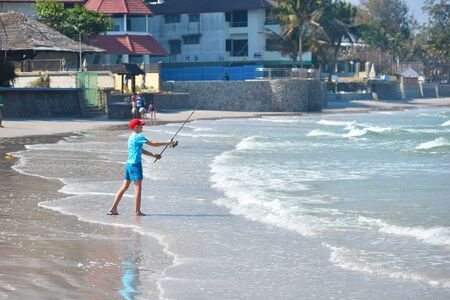 Fishing with his son on the shore. A quiet holiday at sea. Active vacations at sea. Boy with a homemade fishing rod.