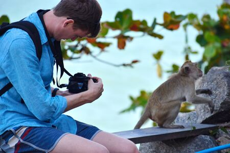 Travel photography in Asia. A tourist takes pictures of the monkey.