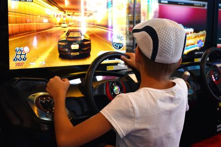 Racing car simulator. A little boy plays virtual games. Of computer racing.