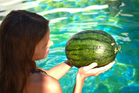 Funny watermelon with glasses. The little girl in the pool playing. Cheerful child with a watermelon. Archivio Fotografico - 137427827