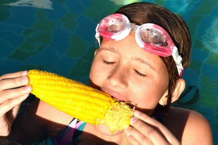 Cute girl in water glasses with corn. Boiled corn in the pool. To feast on a juicy corn on the sea. Reklamní fotografie