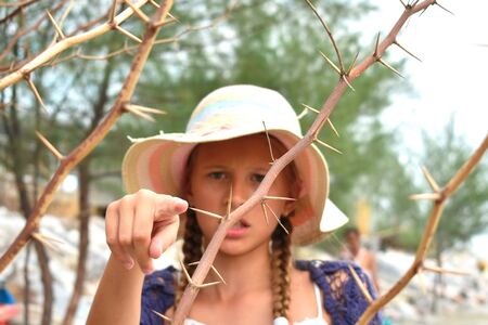 The girl in the hat in the dangerous bushes. Little girl and spikes. Stock Photo