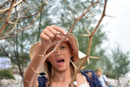 The girl in the hat in the dangerous bushes. Little girl and spikes. Stock Photo - 137878847