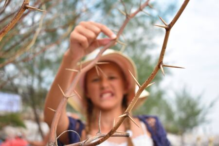 The girl in the hat in the dangerous bushes. Little girl and spikes.