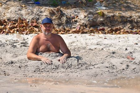 lone Vacation on the beach. Full man buried in the sand