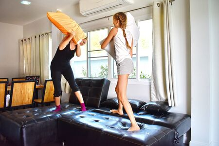 Mother with daughter playing on bed. Happy motherhood. Family learning at home. games with pillows.