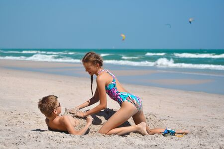 Brother and sister playing on the beach. Happy children of the sea