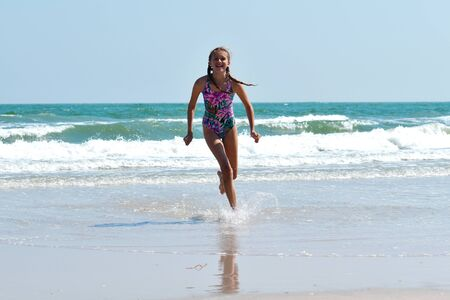 Teen girl running on the beach. Happy child on the sea