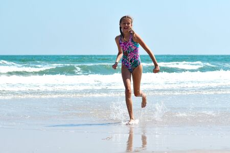 Vacation at sea with children. Baby girl running at sea beach. Reklamní fotografie