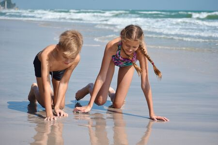 Happy children play together on the beach.