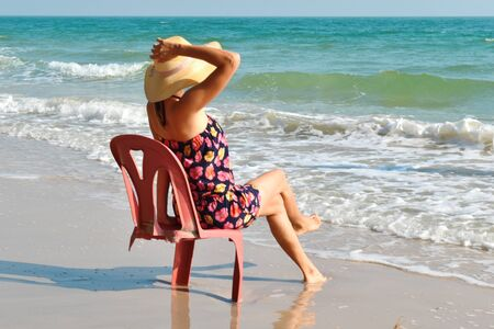 beautiful girl on a chair on the coast