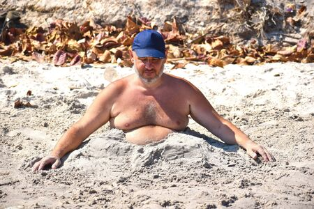 Funny fat man sleeping on a public beach.