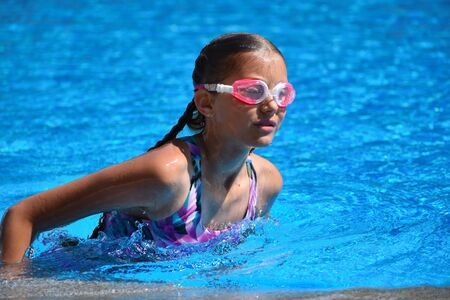 Cute girl enjoys in swimming pool at the hotel. teenager at resort in water. swimming training. Holidays with children at sea.