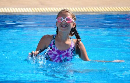 A little girl enjoys swimming in the pool. A water pool in the hotel. Children's summer vacation.