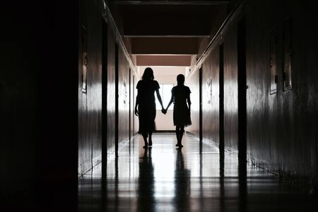 Silhouette of two girls in a dark room.