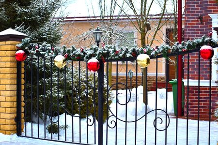 Winter Christmas decoration on the fence of the house. Beautiful New years balls on the fence of the cottage Banque d'images