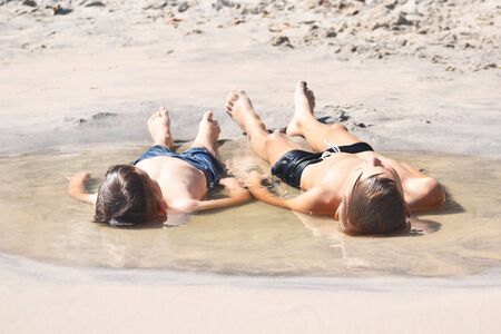 Children lie on the sand. The boys sunbathing in the water. Childhood in the puddle. Direct child