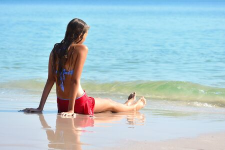 model teenager on the beach. a tropical Paradise for children. Girl in swimsuit at sea. Summer vacation in the tropics.
