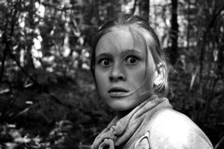 Monochrome photo. Fearful glance of the girl. Child one in the forest is afraid of