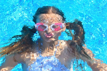portrait of a girl underwater. The child in the water during the summer. Interesting photo