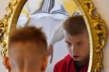 The child reflected in a distorting mirror. A fun reflection of the boy. Childrens entertainment