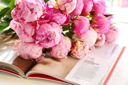 Pink peonies and book. Reading your favorite book. Flowers background. Flowers lie on open book.