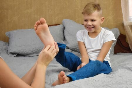 Tickle the child. Happy mother and son on the bed. Funny motherhood.