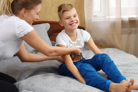Mother tickling son. The parent teases the child. Fun games with mom. Mother and son on bed