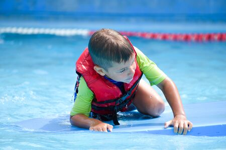 Safe action in the pool. Life jacket on the boy. Saving the child from the water Foto de archivo