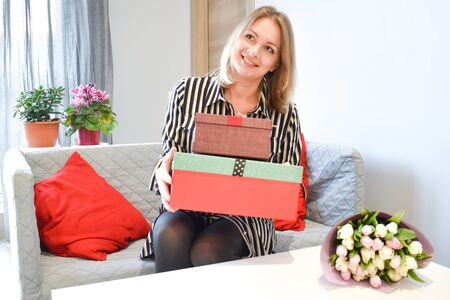 Beautiful girl opens a gift box at home. To give a gift for the holiday.