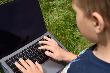 Boy child learning online outdoor. Family education at home. Distance learning on laptop.