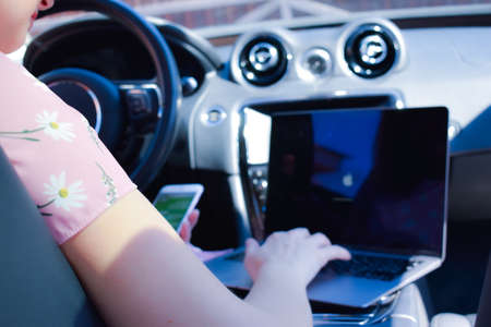 Work in the journey. Professional woman inside an expensive car. Working environment.
