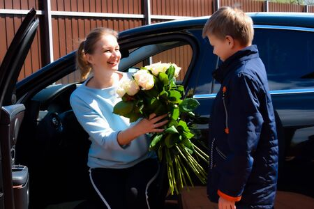 son gives a bouquet of roses to mother. Happy mother with child son