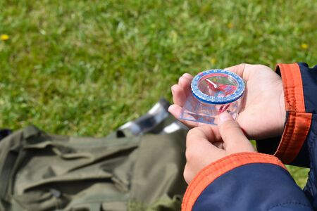 compass in the hand of a child traveler. Orienteering. Hiker boy going camping.