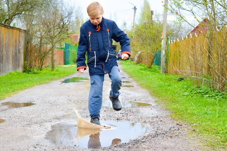 Boy child runs into a wet puddle. Funny walk.
