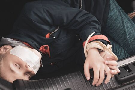 Kidnapped boy in the car. Related children's hands. stealing people