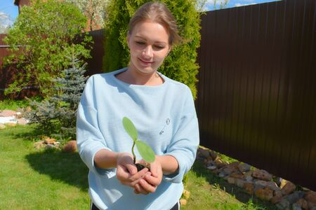 The woman holds in her hands a small plant. Gardening Planting vegetables Reklamní fotografie
