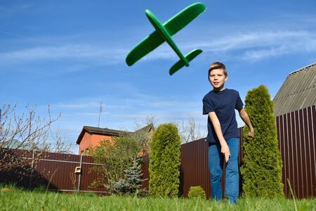 Child boy throws a light aircraft in the air. Children playing on the lawn. Kid boy playing in the garden Stok Fotoğraf