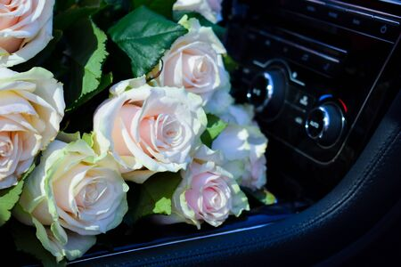 Bouquet of delicate roses on the car seat. Flower delivery service.