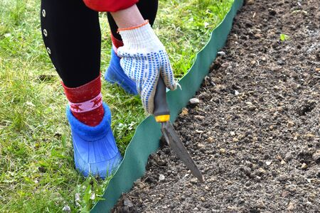 The gardener outdoors. horticulture outside. Woman with garden tool