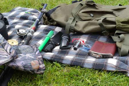 Things hunter on the grass. A necessary set of items for natural extreme travel. Archivio Fotografico