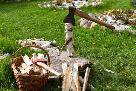 woman with ax chopping firewood on the grass. rustic active lifestyle
