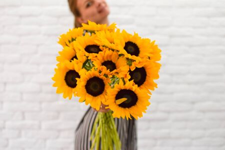a large bouquet of yellow sunflowers in the hands inside